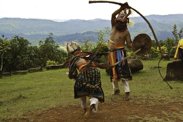 Local villagers performing a tribal dance ritual on an island in Indonesia.