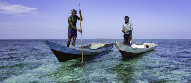 Two mean in canoes navigating the shallow shoreline waters of Indonesia.