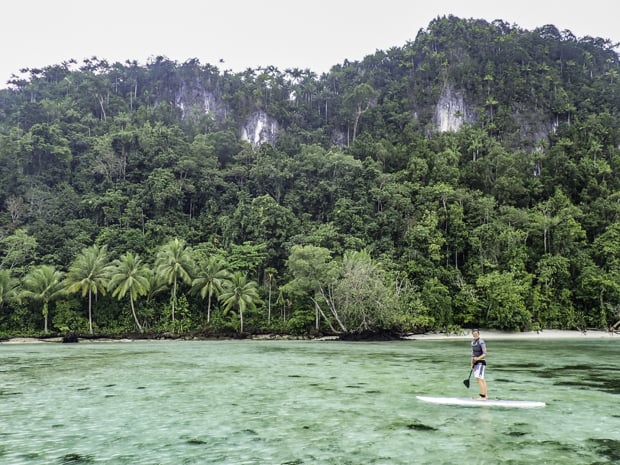 A person paddle boarding along an island shoreline in Indonesia.