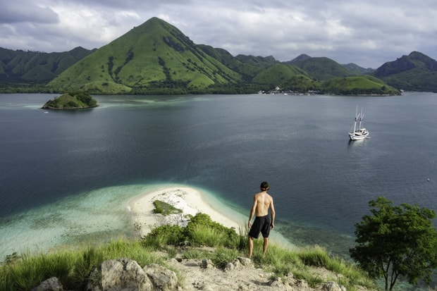 A man looking out over the island at a small ship in Indonesia.