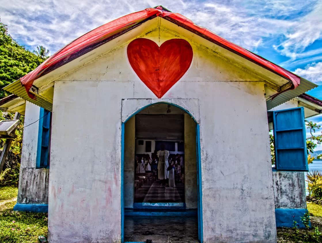 Small church with a red heart painted above the entrance on an island in the south pacific.