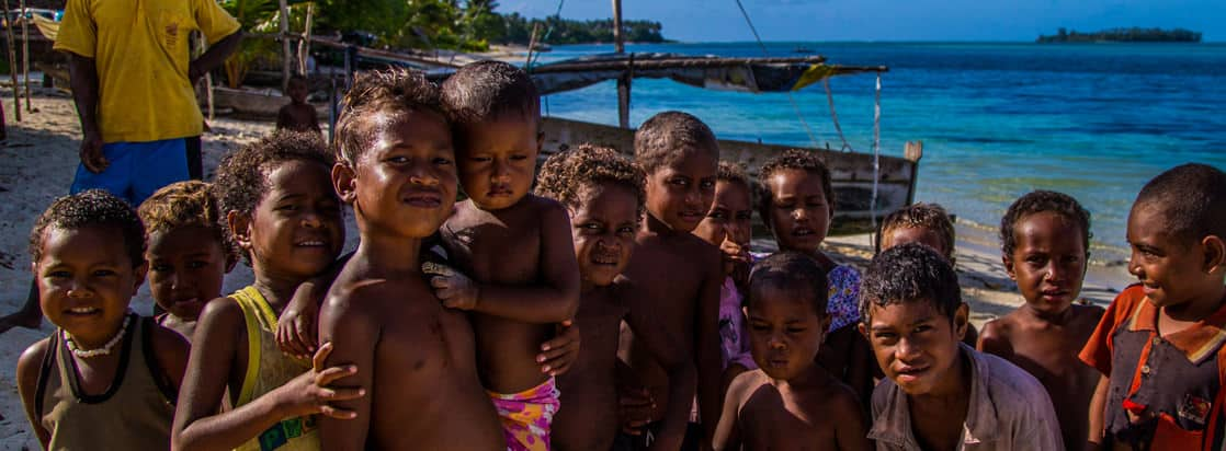 Local kids smiling and posing on a beach in the south pacific.