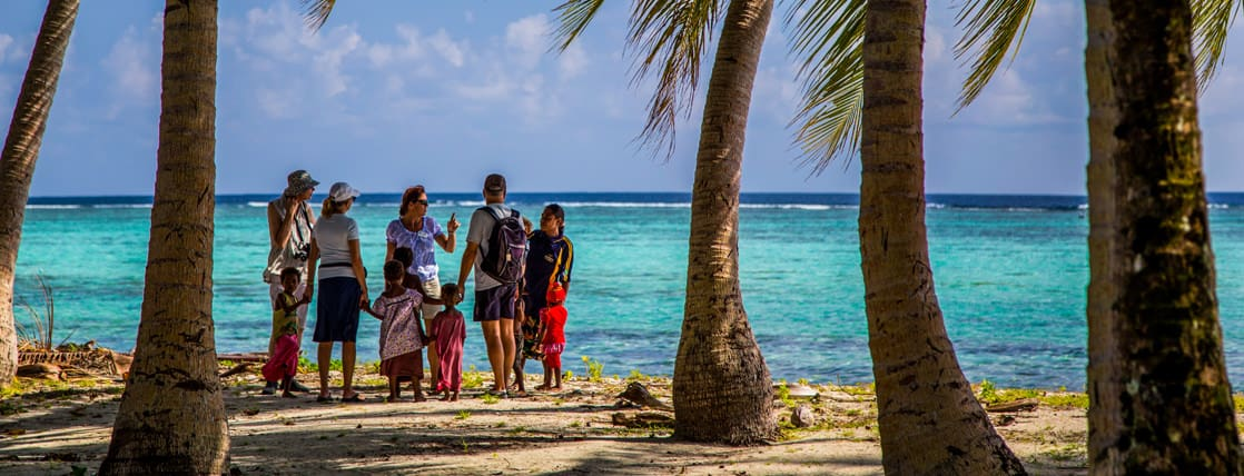 Guests from a small cruise ship talking with locals on the beach in the south pacific islands.
