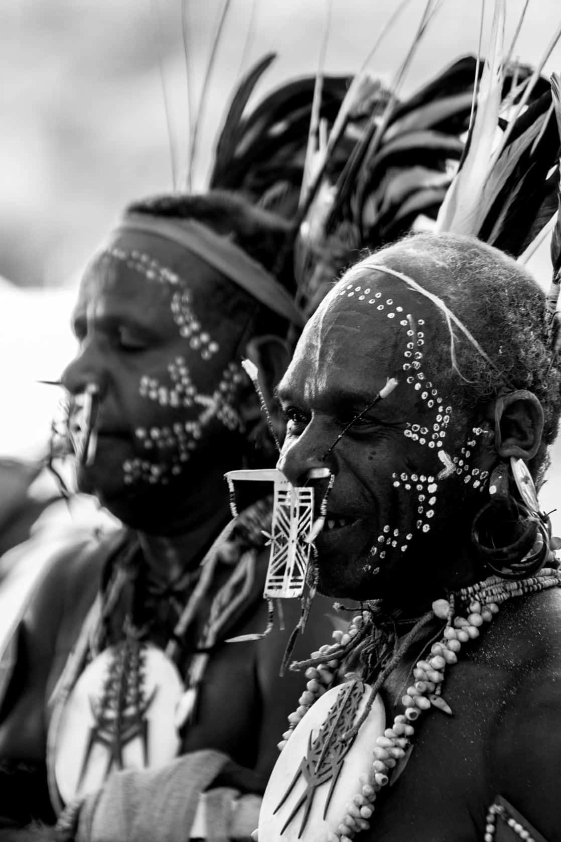 Tribal mean wearing face paint and piercings on an island in the south pacific.