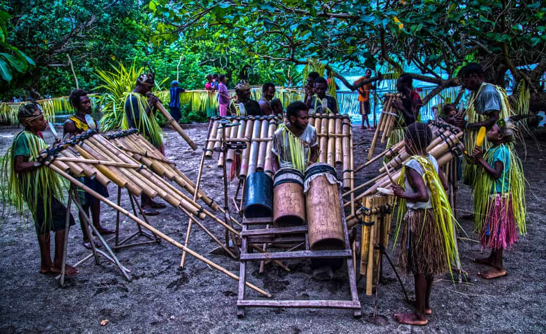 Villagers playing musical instruments on an island in the south pacific.