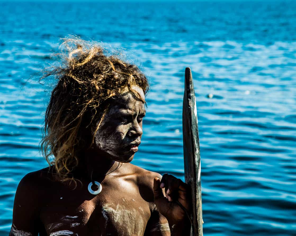 Local warrior in a community in the South Pacific islands with painting on his body and the ocean in the background.