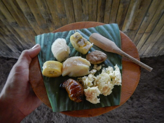Plate of seafood and bananas on a banana leaf with wooden spoon.
