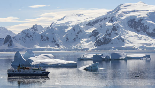 A small ship cruises among icebergs and snow-covered mountains in Antarctica