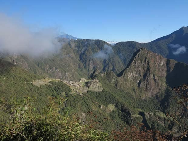 Landscape view of Peruvian mountain ranges with Machu Pichu on the mountainside in the distance.