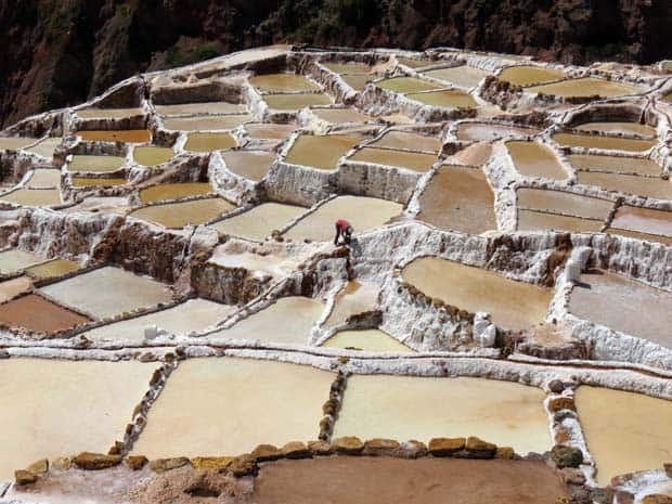View of terraced land surfaces with a single man working the site.