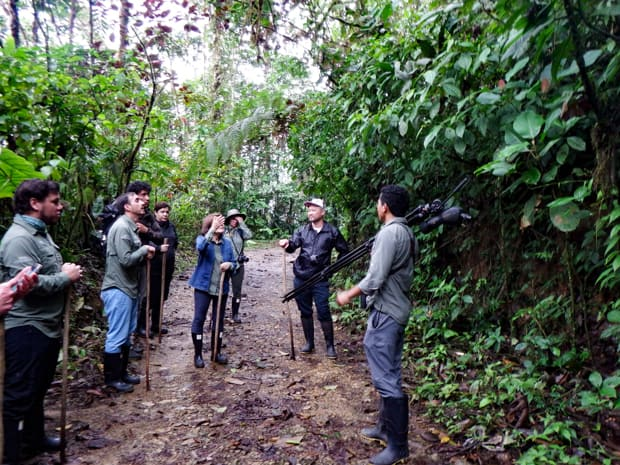 Group of travelers in Ecuador walking on a muddy trail in the rainforest with a guide.