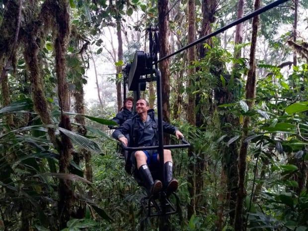 Happy travelers on a open air gondola gliding through the rainforest.
