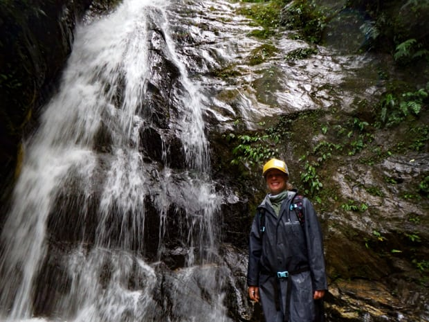 A traveler in Ecuador standing next to a waterfall with green moss on granite rocks.