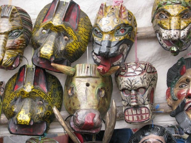 Colorful Mayan mask reproductions of animals, skeleton and male heads.