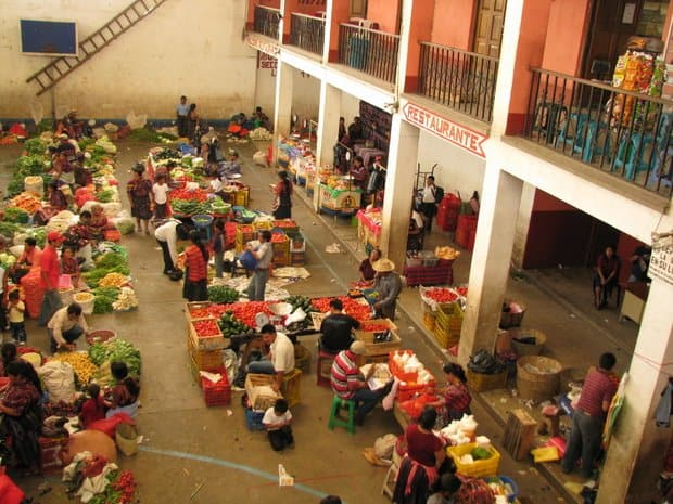 Local fruit and vegetable market bustling with people in a courtyard of building.