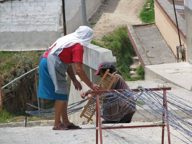 2 local women weaving textiles.
