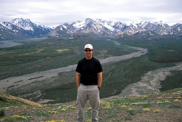 Alaskan traveler posing on top of a mountainside with wildflowers, wild muddy rivers and snow capped mountains.