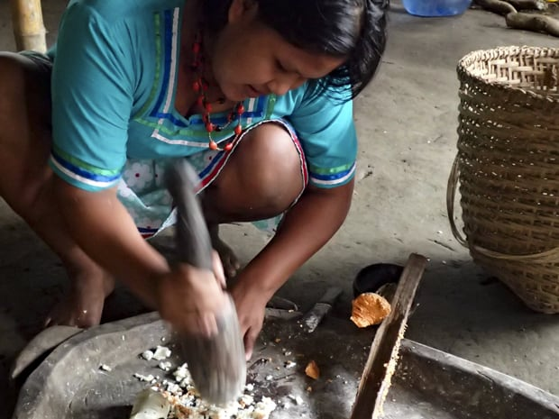 A aboriginal woman making a meal in  a large native stone pan.