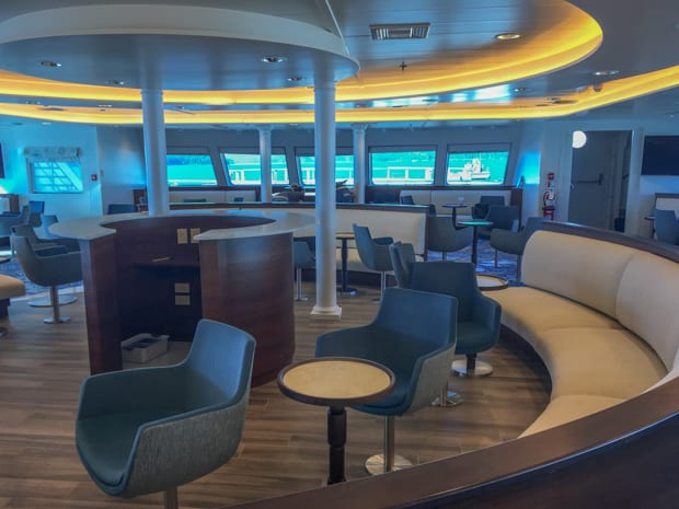 Interior lounge of National Geographic Quest with booth seating and podium