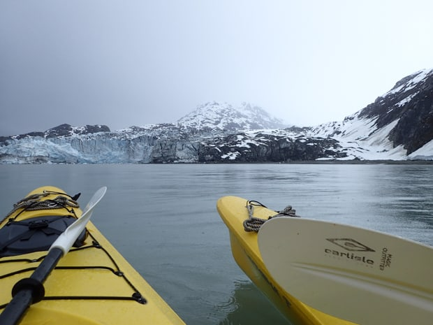 2 kayaks floating on the water in Alaska in front of a tidewater glacier.