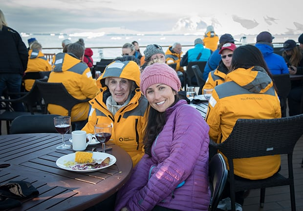 Guests aboard small ship in Antarctica enjoy a bbq on the deck of the ship and drinking wine with icebergs in the background.