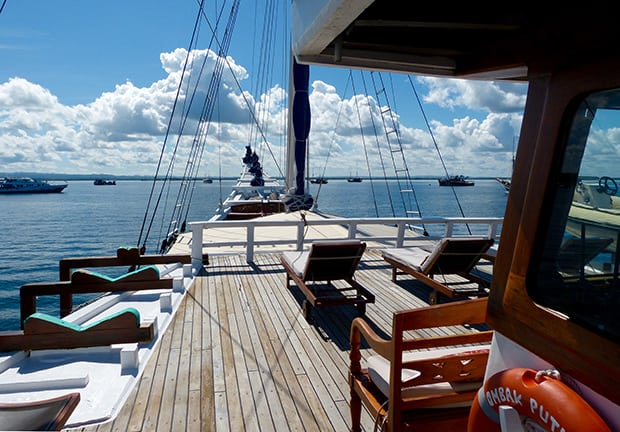 Bow of the Ombak Putih with lounge chairs on deck as it sails through Indonesia.