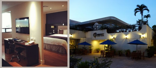 Inside a room at the Oro Verde hotel with desk and bed and outside view of the outdoor patio.