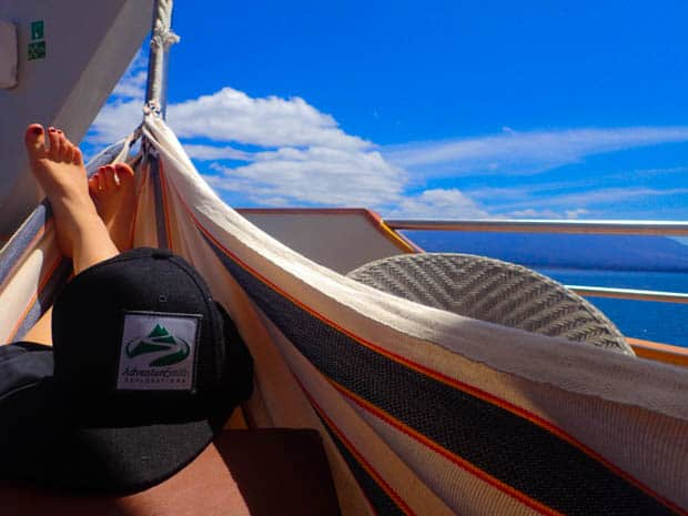 Galapagos passenger on the small ship cruise Origin relaxing in a hammock on a balcony deck enjoying the view of the ocean and outlying islands.