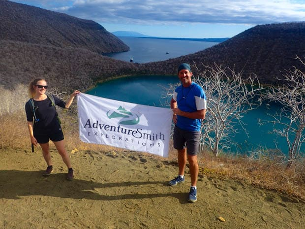 Galapagos travelers holding the Adventuresmith Explorations flag on the bluff overlooking Sullivan bay.