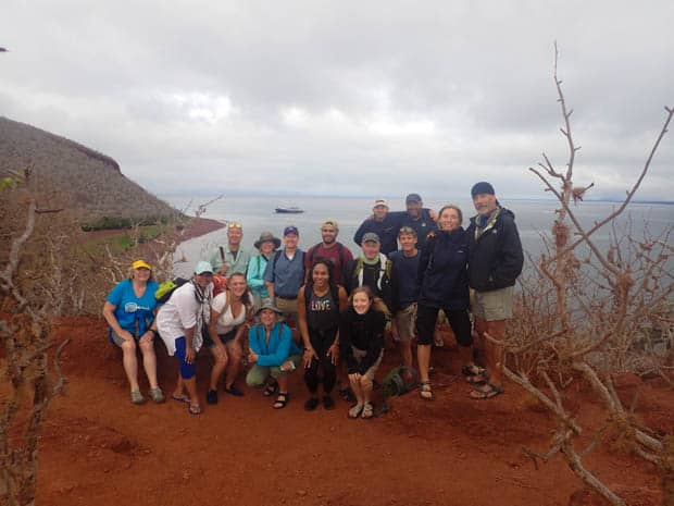 Group of happy travelers on a bluff with on a Galapagos Island hike with the Origin in the background.