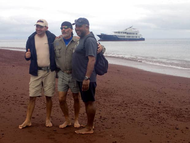 Origin crew on the beach with the small ship cruise Origin anchored off the shoreline.