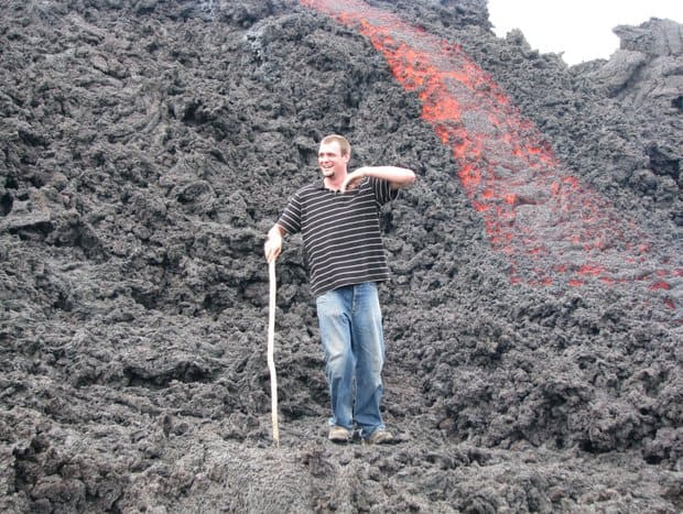 Happy young traveler walking down volcanic rock with hot lava running underneath volcanic rock next to him.