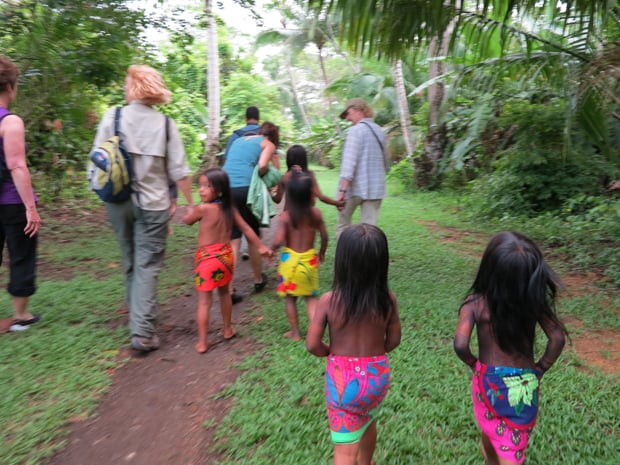 Guests walking with local children on a tour in a village from a small ship cruise in Panama.