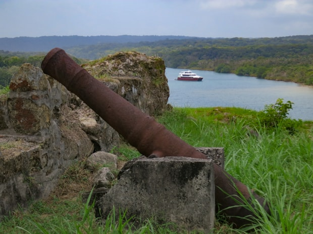 An old canyon in a historic park  in Panama with a small cruise ship in the background.