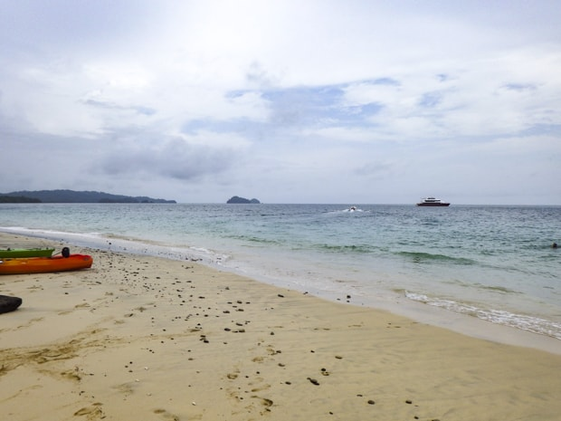 Kayaks resting on the beach at the pearl islands with a small ship in the background.