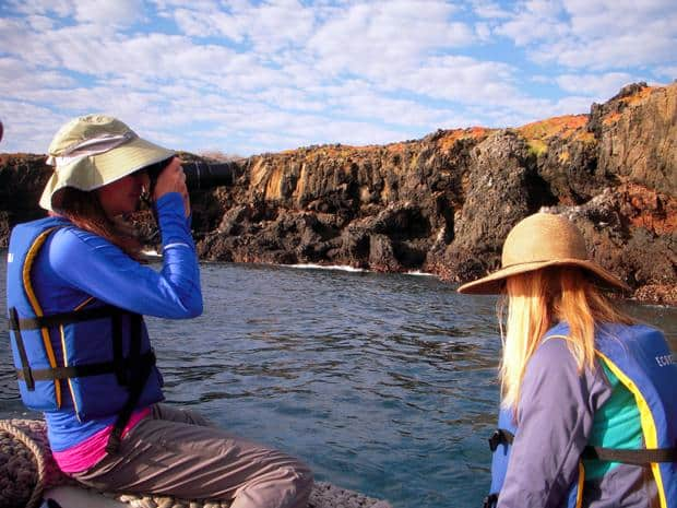 2 travelers viewing the rocky, colorful shoreline from the zodiac in the Galapagos.