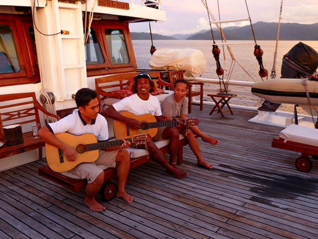 Three crew members playing guitar and singing on deck aboard the small ship Ombak Putih.