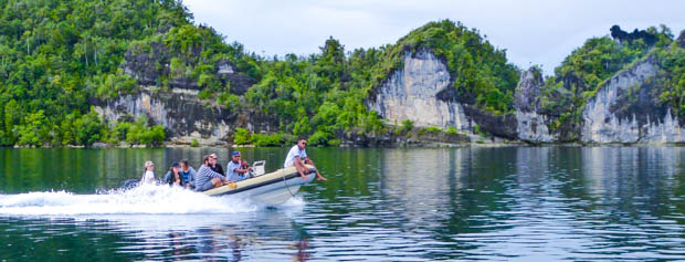 Guests taking a skiff off a small ship cruise to explore islands in Indonesia.