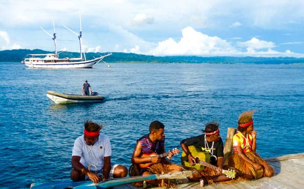 Locals playing music on the dock in Indonesia with a small ship in the background.