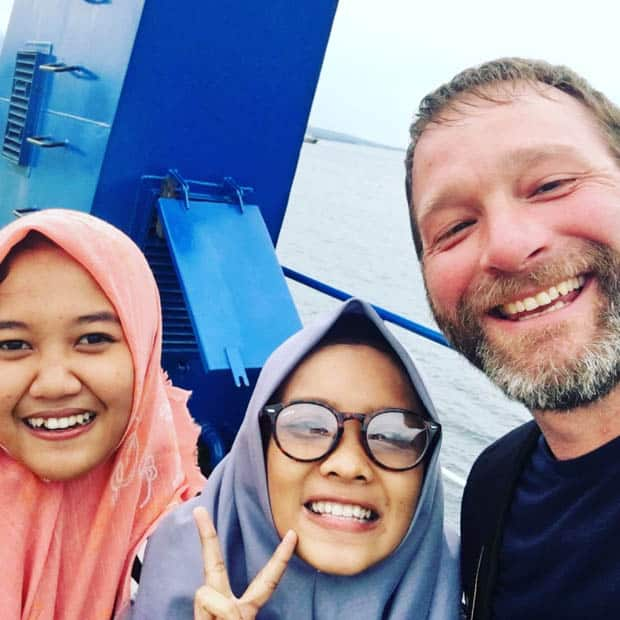 Happy guest aboard the small ship Ombak Putih smiling with two Indonesia women.