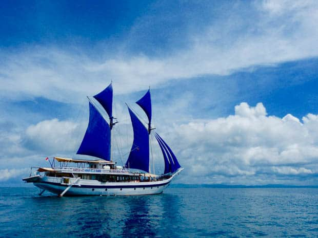 obak putih small ship cruising through the blue waters of Indonesia with her sails up.