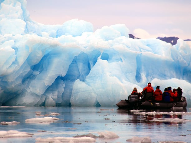 Group of Arctic travelers in a zodiac looking at a giant iceberg.