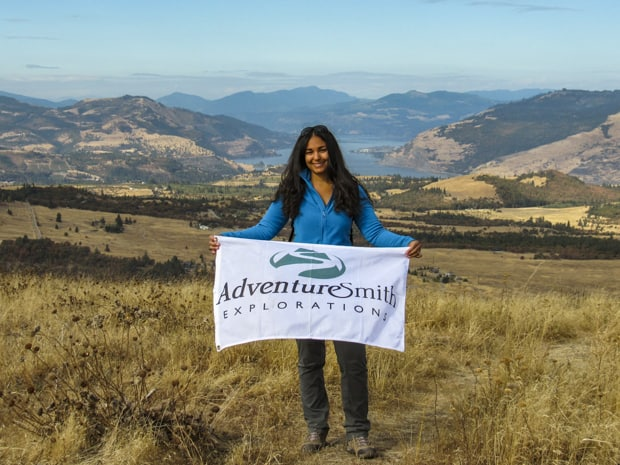 Guest posing with an AdventureSmith Explorations flag at a viewpoint on their hike in the Pacific Northwest.