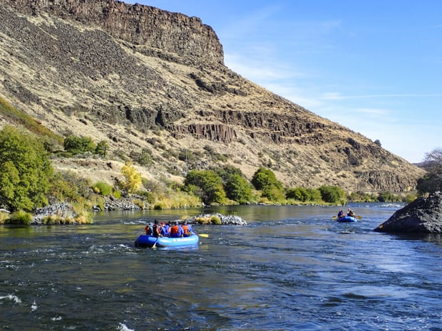 Guests on a river cruise tour floating in rafts on the Deschutes River