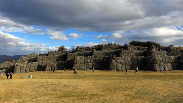 View of a Inca stone ruin with tourists walking about on a Peruvian land tour.