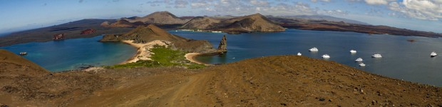 Panoramic view of Bartolome Island with small boats and yachts anchored, rock formations, a hourglass sandy shoreline.