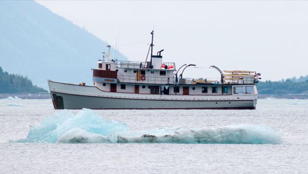 An 8-guest adventure yacht sails behind a blue iceberg in Alaska