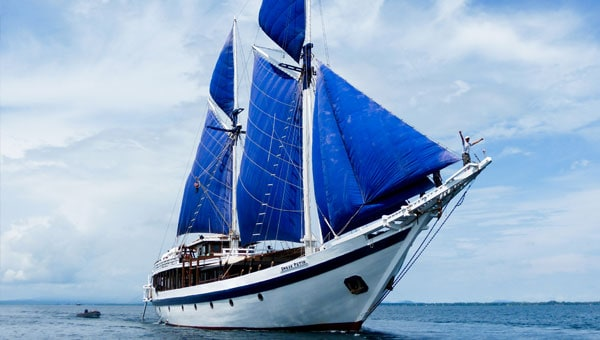 A small ship with blue sails cruises in Indonesia