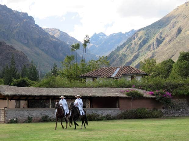 Hotel in a valley floor with large mountain ranges on either side and 2 cowboys riding horses on a lawn.