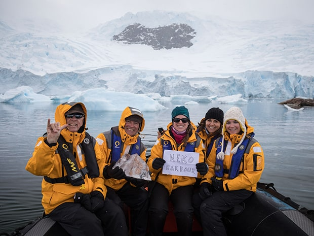Guests from a small ship on a skiff excursion in Neko Harbor, Antarctica holding up signs and smiling.